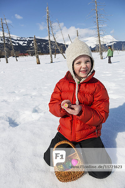 Young girl showing off her found Easter eggs while sitting in snow  Alaska Wildlife Conservation Center  Southcentral Alaska  USA