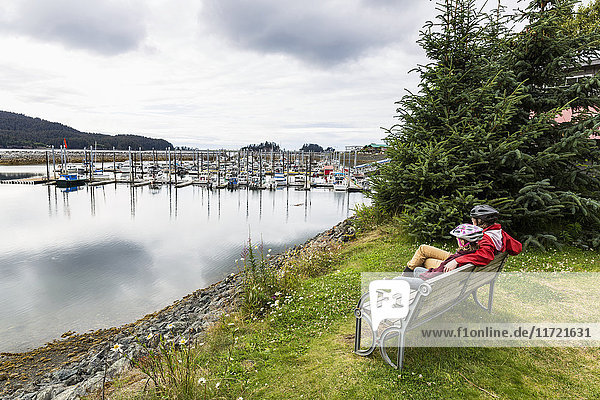 Mother and daughter relax on a bench overlooking the Seldovia small boat harbor  Southcentral Alaska  USA
