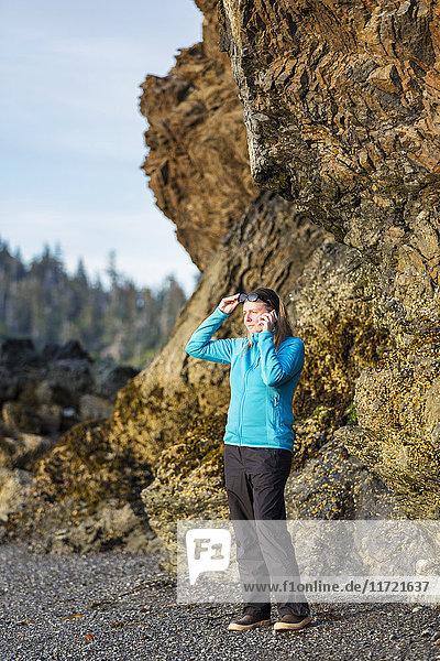 Woman talking on a cell phone along a Homer beach  Kenai Peninsula  Southcentral Alaska  USA
