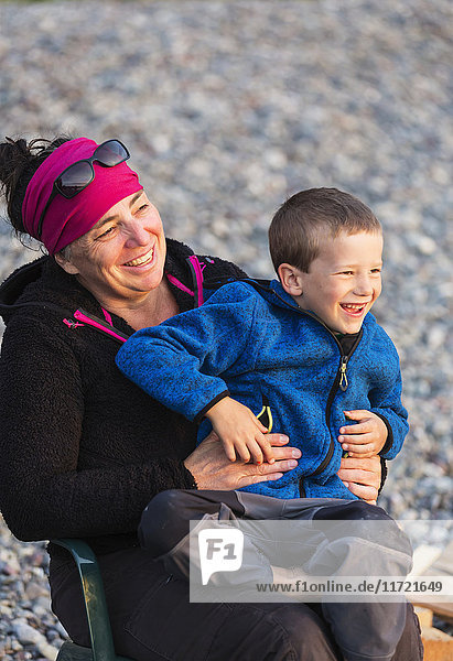 Mother and son in a camp chair on the beach of Hesketh Island  Southcentral Alaska  USA