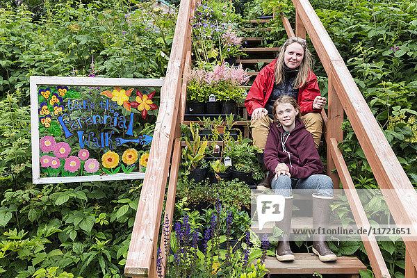 Mother and daughter sit on steps among a lush garden  Seldovia  Southcentral Alaska  USA
