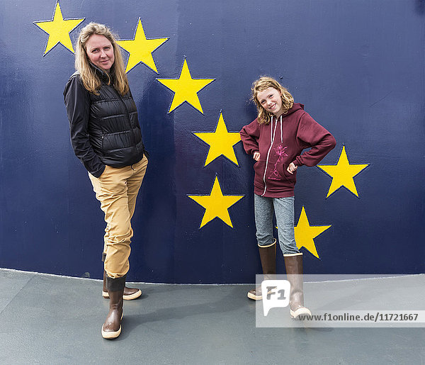 Mother and daughter in rubber boots stand on the deck of the Alaska Marine Highway M/V Tustumena  Homer  Southcentral Alaska  USA