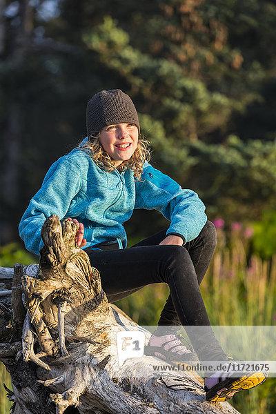 Young girl sitting on driftwood along the beach  Seldovia  Southcentral Alaska  USA