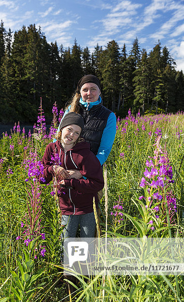 Mother and daughter standing in a field of tall Fireweed  Seldovia  Southcentral Alaska  USA
