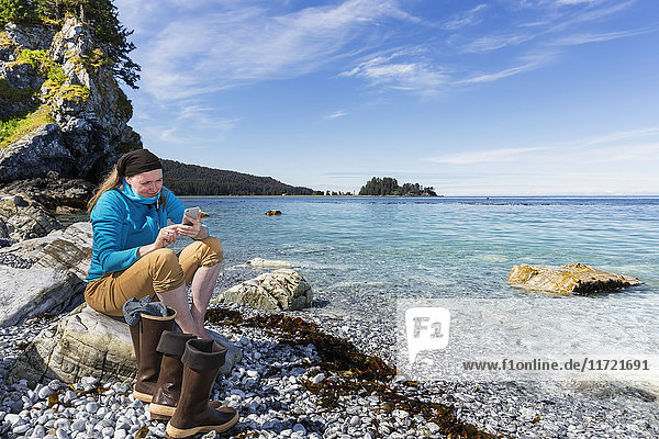 Woman texting on a cell phone along the shore near Seldovia  Southcentral Alaska  USA