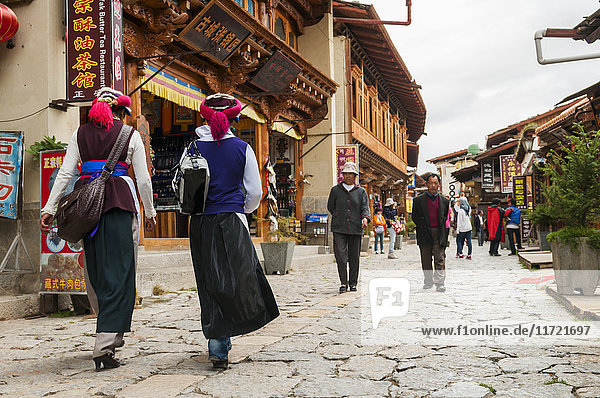 'An ancient street from Shangrila's old town  two women from a minority group walking; Shangri-La  Yunnan province  China'