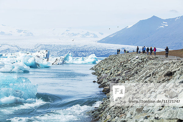 'A group of tourists stands at the edge of a viewpoint at glacier lagoon  Jokulsarlon in the south of iceland  one of the most popular tour highlights in Iceland; Jokulsarlon  Iceland'