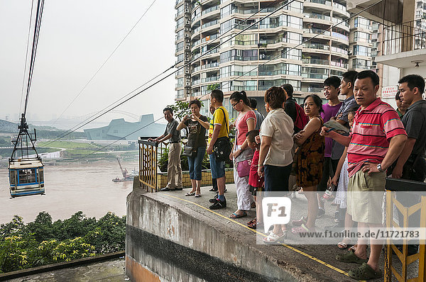 'Passengers waiting for the cable car for crossing Yangtze river in Chongqing  the city as background covered by the fog; Chongqing  China'