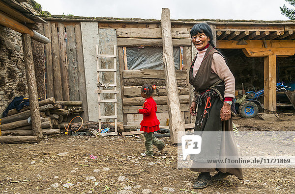 'A woman and her grandddaughter outside a traditional Tibetan house; Daocheng  Sichuan province  China'