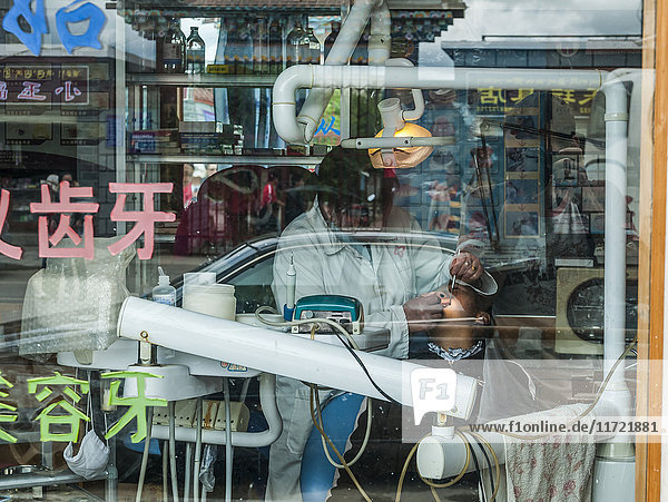 'A dentist visit in Shangrila city  not very private and everyone can see you from the window of the dental office; Shangrila  Yunnan province. China'