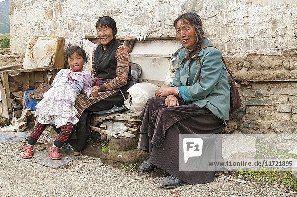 'Two Tibetan women and a young girl sitting beside a wall; Daocheng  Sichuan province  China'