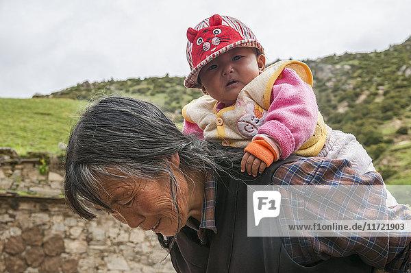 'Portrait of a Tibetan women and baby girl; Daocheng  Sichuan province  China'