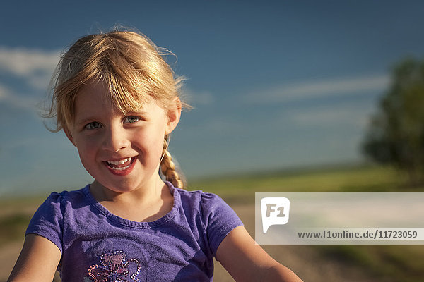 'Close up portrait of a young girl with blond hair and a rural landscape in the background; Herschel  Saskatchewan  Canada'