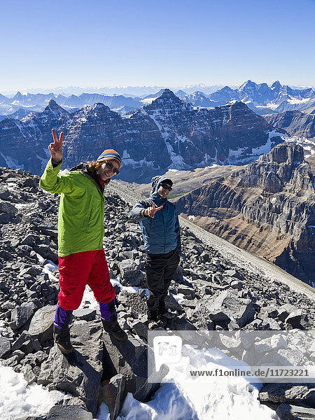 'A young man and young woman posing while climbing in the Rocky mountains; Banff  Alberta  Canada'
