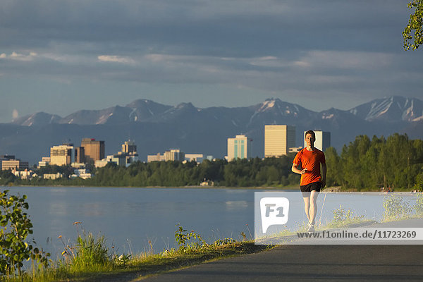 'Man Jogging On The Tony Knowles Coastal Trail During High Tide With The Anchorage City Skyline  Knik Arm  And Chugach Mountains In The Background; Anchorage  Alaska  United States Of America'