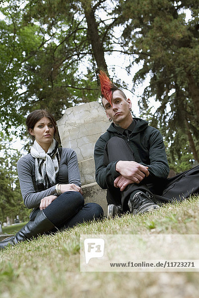 'A Young Man And Young Woman Sitting By A Tombstone In A Cemetery; Edmonton  Alberta  Canada'