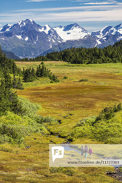 'A small group of women hiking along a stream in Turnagain Pass  with patches of snow on the Chugach Mountains in the background; Alaska  United States of America'
