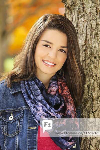 'Portrait of a young woman standing against a tree trunk with autumn colours in the background; Oregon  United States of America'