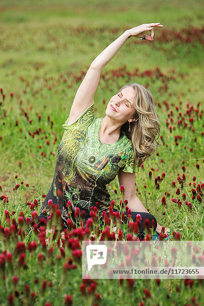 'A woman does yoga in a field of wildflowers; Oregon  United States of America'