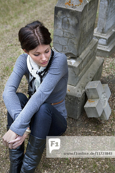 'A Young Woman Sits Leaning Against A Tombstone; Edmonton  Alberta  Canada'