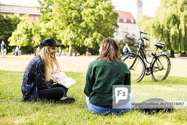 Two young women sitting in park and studying Two young women sitting in park and studying