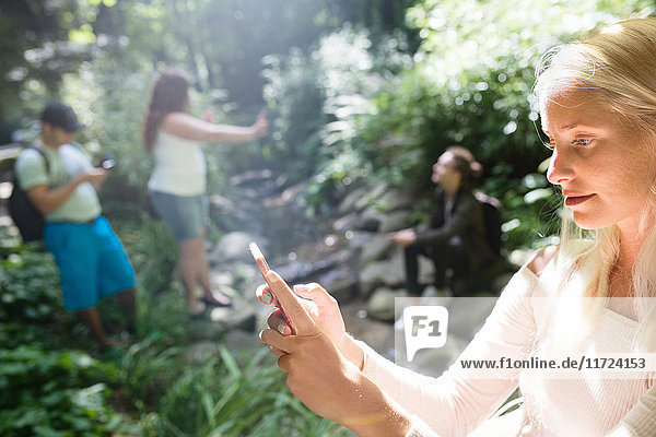 Group of friends playing augmented reality game with mobile phones in park