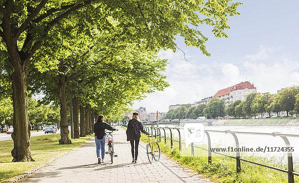 Two young women walking along river and pushing bikes Two young women walking along river and pushing bikes