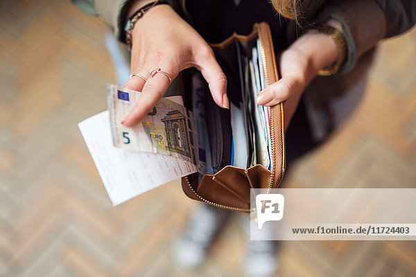 Woman holding open wallet with banknotes and receipts Woman holding open wallet with banknotes and receipts