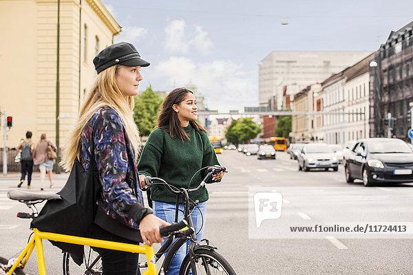 Two young women pushing bikes in town