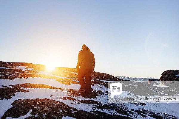 Rear view of man walking on snow