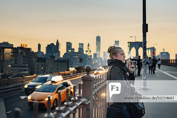 Woman standing on bridge and smoking cigarette  cityscape in background