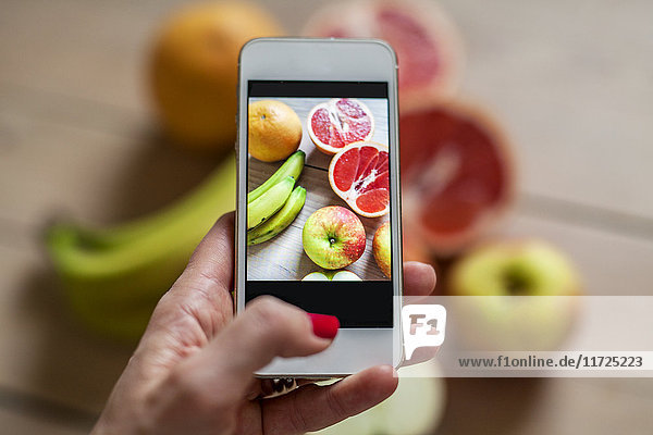 Woman photographing fruits
