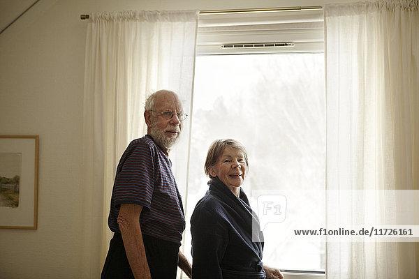 Senior couple standing next to window
