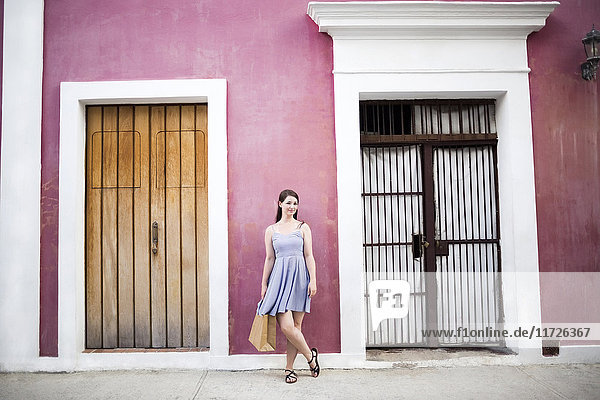 Puerto Rico  San Juan  Woman with shopping bag standing in front of pink building