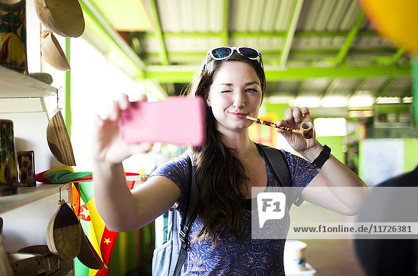 Caribbean Islands  Grenada  woman taking selfie with pipe in souvenir shop