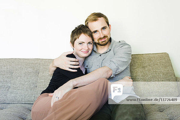 Couple looking at camera and embracing on sofa