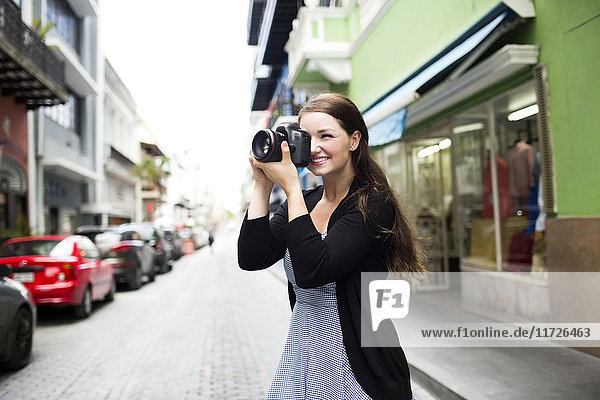 Puerto Rico  San Juan  Woman photographing buildings on street