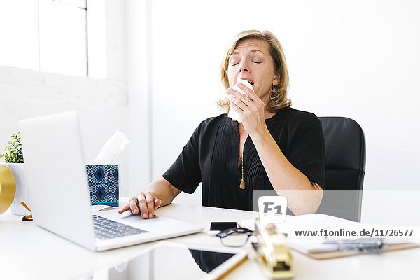 Woman using laptop and sneezing