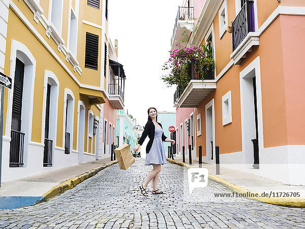 Puerto Rico  San Juan  Woman with shopping bag walking city streets