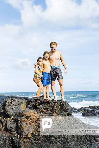 Man and children (6-7  8-9) standing on rock by sea