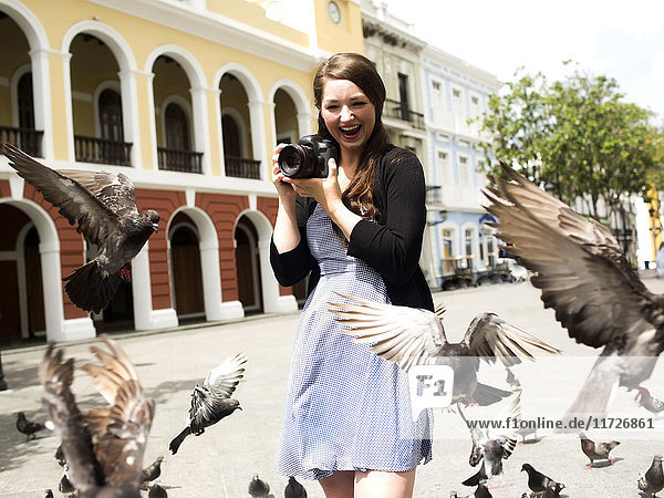Puerto Rico  San Juan  Woman standing on street and photographing pigeons