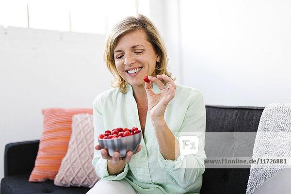 Mature woman eating raspberries