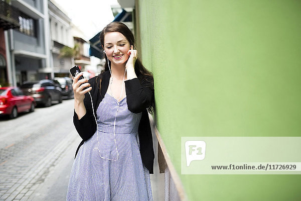 Puerto Rico  San Juan  woman with smartphone and earphones on street