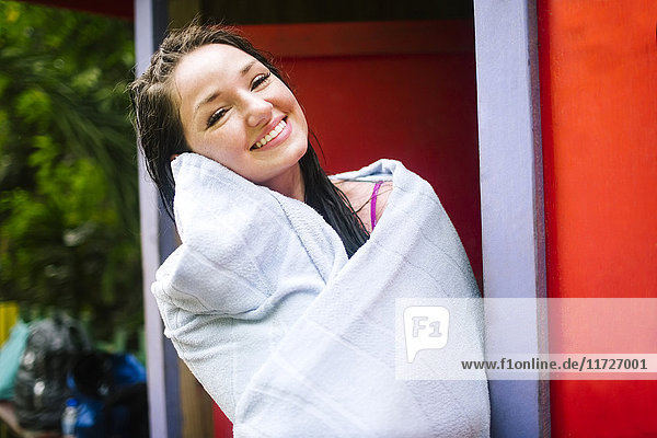 Smiling woman with wet hair wrapped in towel