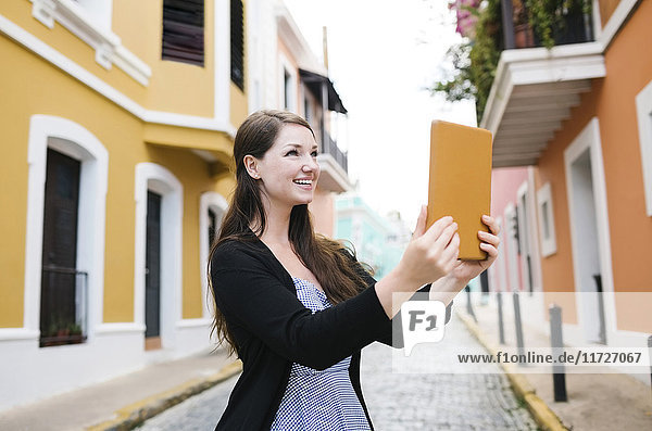 Puerto Rico  San Juan  Woman with tablet doing selfie on city street