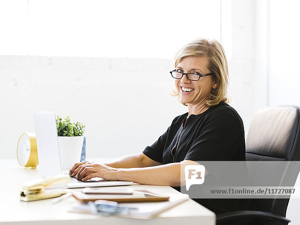 Portrait of Mature woman in office typing on laptop