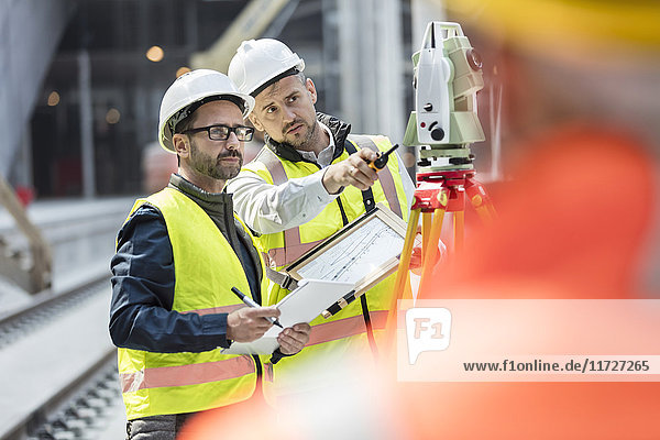 Male engineers using theodolite at construction site