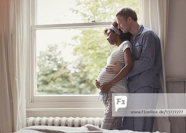Zärtliches schwangeres Paar im Pyjama  das sich am Fenster umarmt