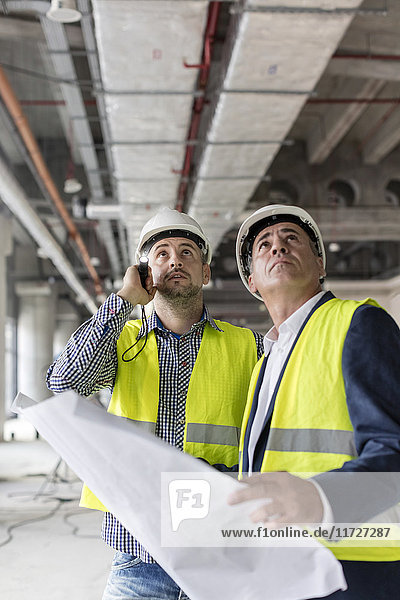 Male engineers with flashlight and blueprints looking up at construction site