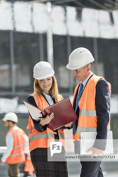 Architekten bei der Überprüfung der Unterlagen auf der Baustelle